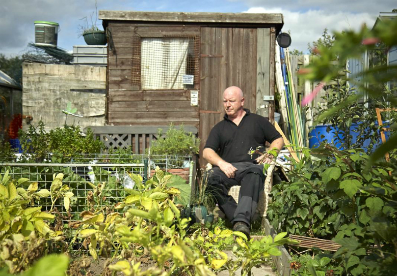 man sitting outside shed on allotment