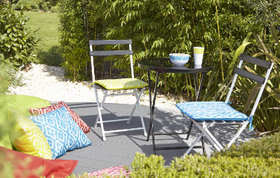 Garden chairs and cushions in sunny garden