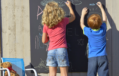 kids drawing on blackboard outside