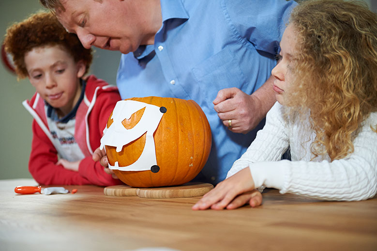 Carve out a face template on a pumpkin