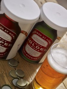 Woodfordes Starter Kit Real Ale 20 Pint showing tubs of different largers bottle caps on table and pint of larger in glass