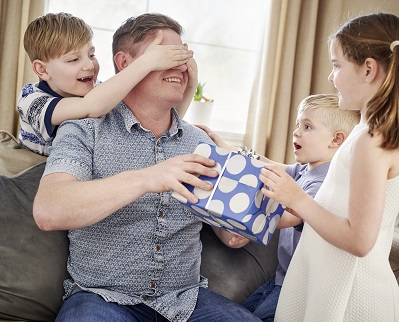kids suprising dad with fathers day present in blue spotty gift box