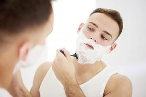 man shaving his face with foam on face holding a shaving razor