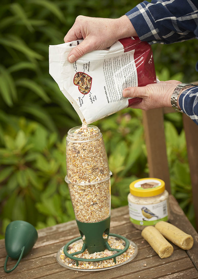 filling wilko bird feeder with bird seed